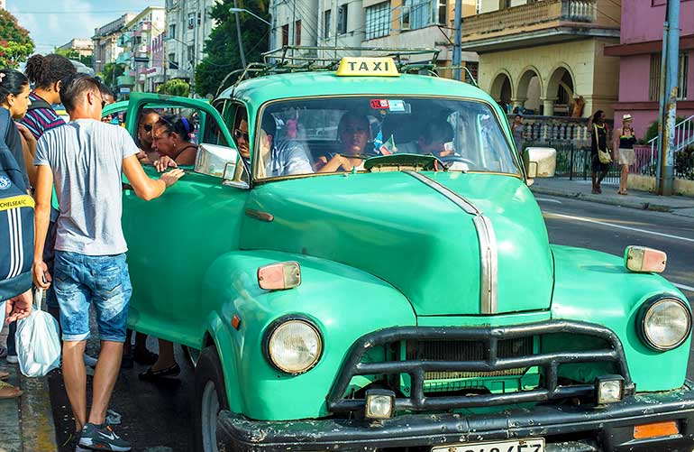 Cubans ride to work in old American car.
